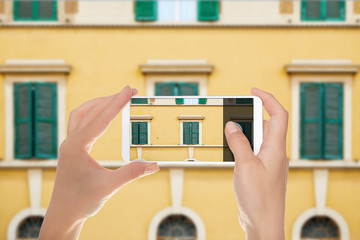 A man is making a photo of pattern from windows of the facade of one of the buildings in Rome, Italy on a mobile phone