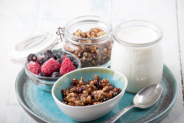 Homemade granola in glass jar   and yogurt in glass  for breakfast