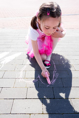 Beautiful little girl drawing a pink heart with chalk on the pavement.