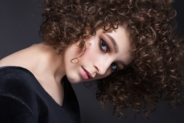 Portrait of a beautiful teen girl with natural make-up and afro curls.