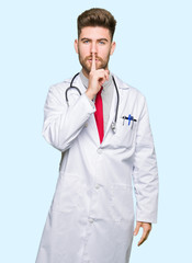 Young handsome doctor man wearing medical coat asking to be quiet with finger on lips. Silence and secret concept.