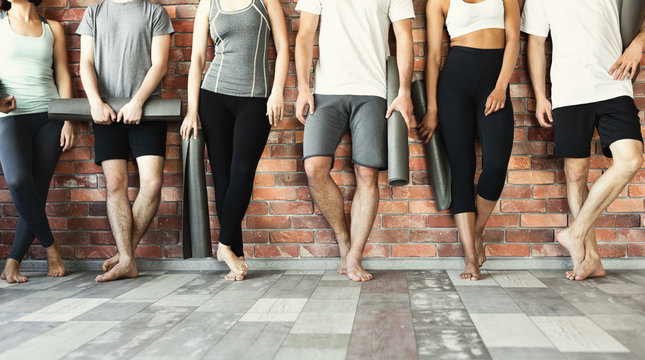 Young people waiting for yoga class in studio.