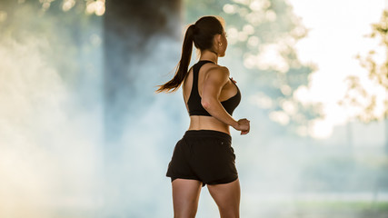 Shot of a Beautiful Fitness Girl in Black Athletic Top and Shorts Jogging in a Foggy Street. She is Running in an Urban Environment Under a Bridge.