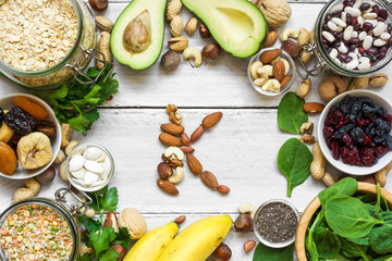 Potassium Food Sources as dried apricot, avocado, bean, chia seeds, banana, nuts, spinach. top view. flat lay