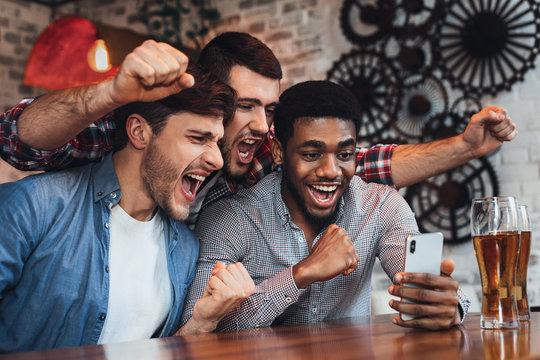 Men watching football on smartphone in bar