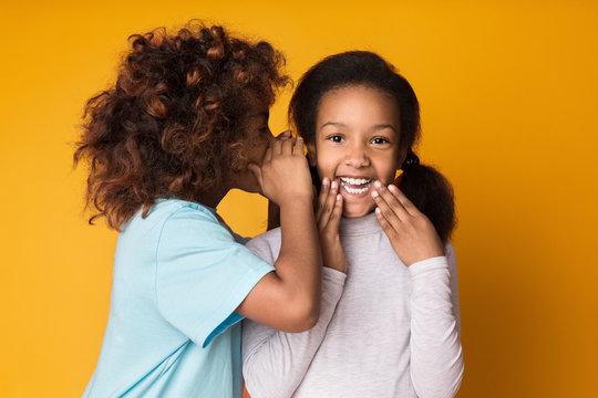 Cute girl telling secret her friend over background
