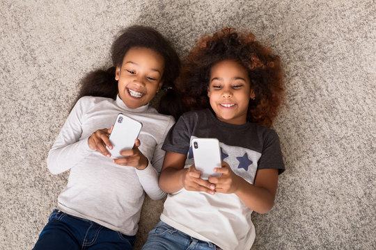 Happy little girls with smartphones lying on floor