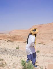 Árabe en su entorno, paseando y observando, de espaldas
