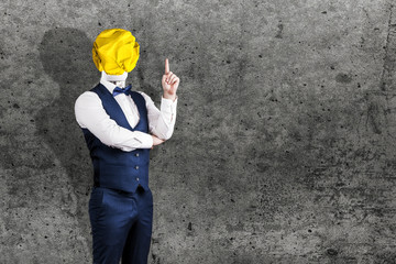 Wall Mural - a man on concrete background in a suit with a light bulb of crumpled yellow paper instead of a head with a raised finger, the concept of the idea