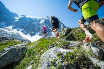 Three trail runners running up a steep trail towards the mountains in the Alps Wall mural