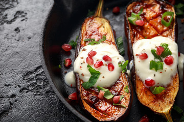 Grilled eggplants with yogurt sauce, pomegranate seeds, parsley and green onion in cast iron vintage pan.