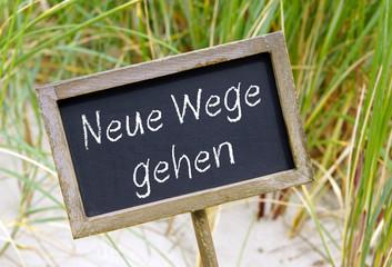 Neue Wege gehen, Schild oder Kreidetafel aus Holz mit Text am Strand