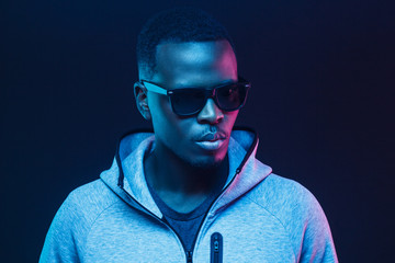 Close-up portrait of stylish black man, wearing hoodie and sunglasses Wall mural