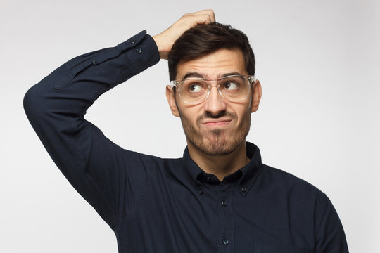 Caucasian man wearing glasses isolated on grey background scratching his head trying to find solution