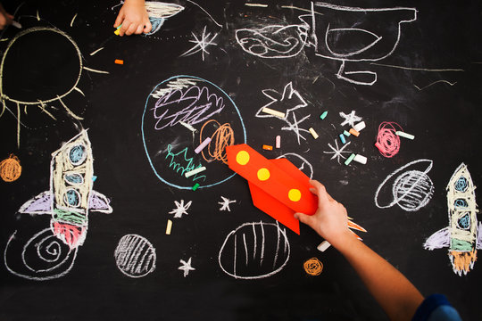 the child draws a rocket and space on a blackboard. preschool Child in creativity in the home.