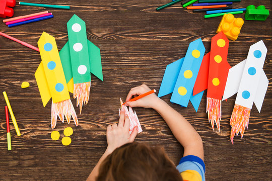 preschool Child in creativity in the home. Happy kid makes rockets from paper. Children's creativity. Creative children play with craft.