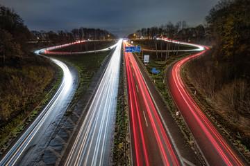 Autobahnausfahrt und Autobahnauffahrt bei Nacht mit Lichtstreifen Fotomurales