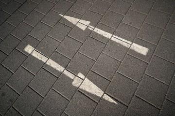 Richtungspfeile auf einer gepflasterten Straße
