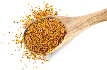 pile fresh bee pollen in wooden spoon isolated on white background, top view