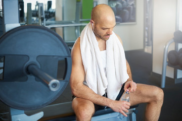 Sporty man relaxing in the gym and drinking a bottle of water