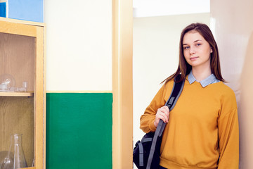 Young confident smiling female college student standing in the doorway at her school, wearing backpack. Education concept.