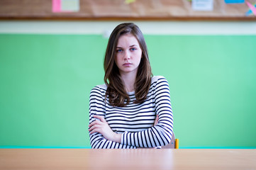 Young depressed and anxious female high school student sitting at her desk in a classroom, with her arms crossed.