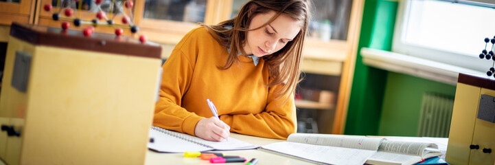 Young female college student in chemistry class, writing notes. Focused student in classroom. Authentic Education concept web banner.