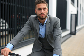 Handsome young businessman riding bicycle outdoors in the city.