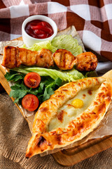 Traditional georgian adzharian khachapuri and meat shashlik with vegetables at decorated wooden board background.