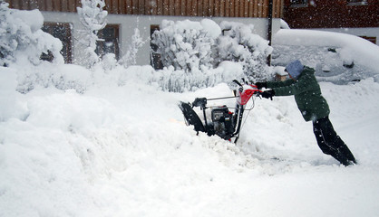 Felix Feldhahn uses a snow blower after heavy snowfall in Warngau