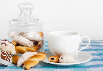 Cup of hot tea with fresh cookies and candy on checkered tablecloth