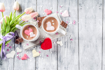Girl hands hold hot chocolate with marshmallow hearts, red pink white color with chocolate pieces, sugar sprinkles, old wooden background copy space top view, hands in pictute flatlay