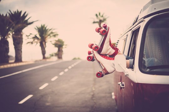 Pair of woman feet with roller blades vintage style over the window of legendary camper van - long road and tropical palms and light in background - freedom and rock'n roll lifestyle pin-up concept