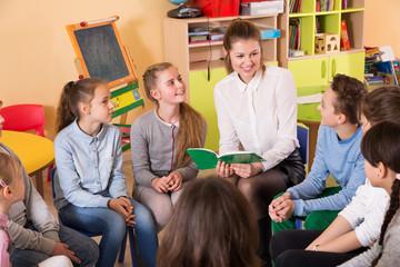 children sitting and listening teacher