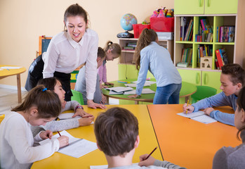 Woman teacher helping to pupils with work at lesson