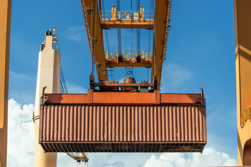 Fototapete - Industrial port crane lift up loading export containers box onboard from truck at port of Thailand,The port crane type's twinlift is the best solution for port operations