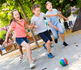 Happy children  playfully running after ball outdoors in park