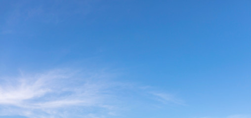 Thin white clouds are floating in the clear blue sky