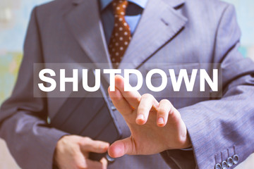 Businessman presses button shutdown on virtual electronic user interface.