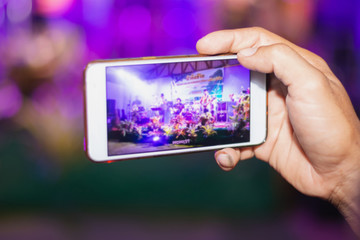 Hands use smartphones record small music concert live streaming video on internet to social media comment chat to Friend