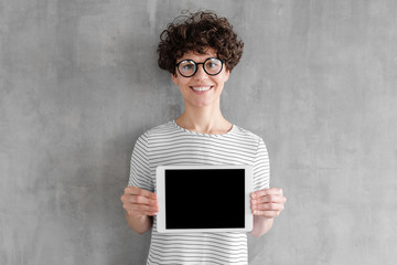 Young beautiful european female showing blank screen of tablet computer with copy space