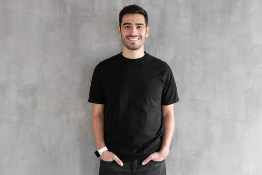 Hotizontal portrait of young man wearing blank black t-shirt and jeans, posing against gray textured wall