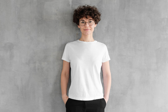 Attractive young woman posing in blank white cotton t-shirt, standing against gray textured wall