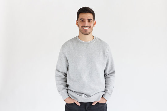 Daylight portrait of young handsome man, wearing oversized sweatshirt, isolated on gray background