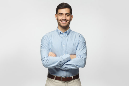 Handsome smiling business man in blue shirt isolated on gray background