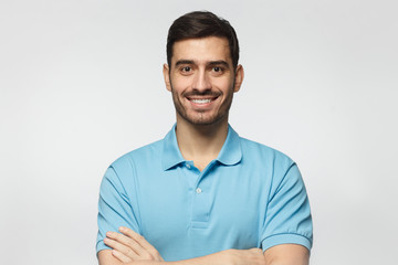 Portrait of smiling handsome man in blue polo shirt, standing with crossed arms isolated on grey background