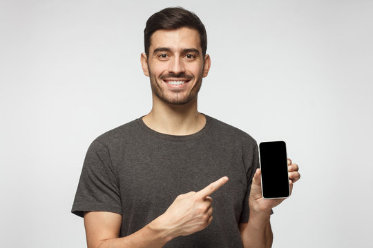 Portrait of happy man demonstrating blank smartphone and pointing to empty screen with smile. Copyspace for yor app
