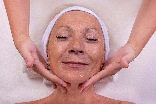 Beautiful smiling senior woman getting a face skin treatment at beauty salon