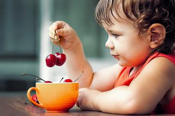 little girl eating a sweet cherry