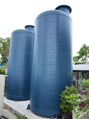 Water storage tank: Two blue water storage tanks made of fiberglass, mounted on a concrete base. For paying water to homes or small businesses